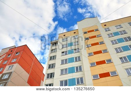 Looking up at the facade of of a multistory apartment house from the concrete panels of red yellow and white on a background of blue sky with clouds.