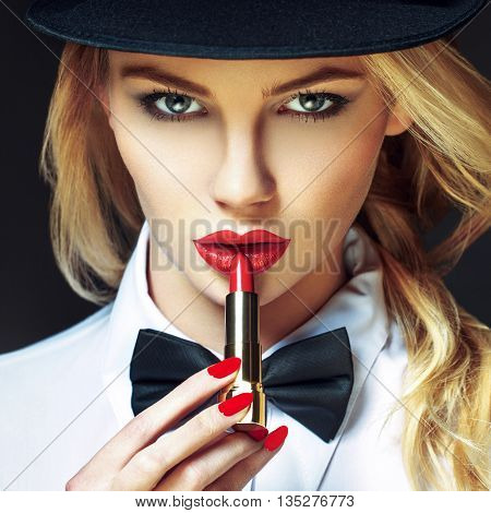 Sexy blonde woman in hat with red lips and nails applying lipstick