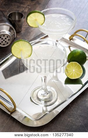 Margarita cocktails on a tray and rustic wooden table