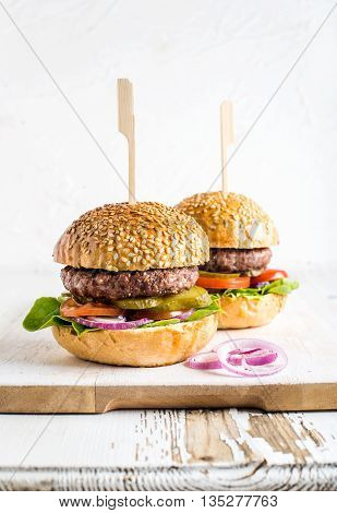 Fresh homemade burgers on wooden serving board with onion rings. White background, selective focus