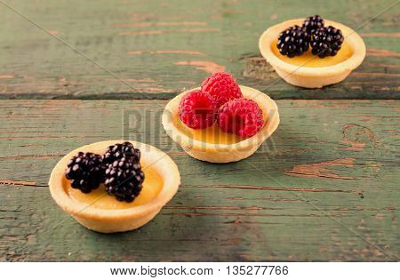 Homemade round tartlets with lemon curd, fresh blackberries and raspberries on wooden table