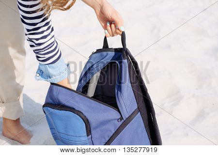 Cropped image: woman's hands opened the blue backpack and pulled out stuff for a picnic on the beach
