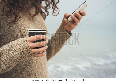 Woman With Curly Hair In A Brown Sweater Walks On The Beach, Using Cell Phone And Drinking Coffee
