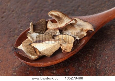 Boletus edulis dry mushrooms on a timber board