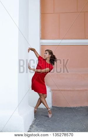 Beautiful ballerina in red dress and in pointe shoes dancing near column