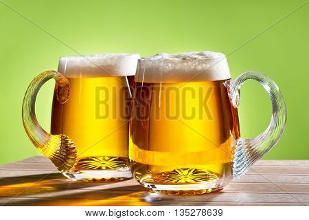two beers on the table with green background