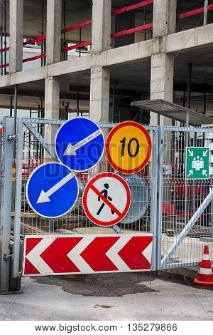 group of road traffic signs on the metal gate of the construction site