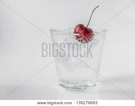 Cherry in glass of soda and ice