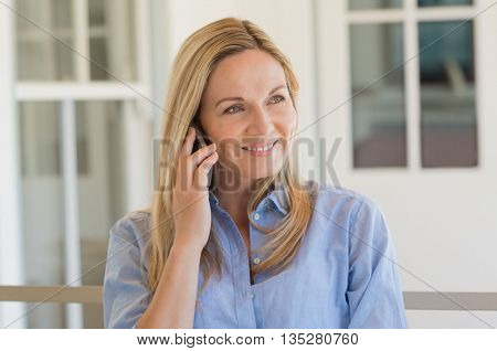 Cheerful mature woman talking over phone outdoor. Happy mid woman using mobile phone. Woman in a happy conversation through smartphone. Smiling woman at telephone.