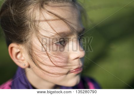 windy hair strands on child girl face by springtime