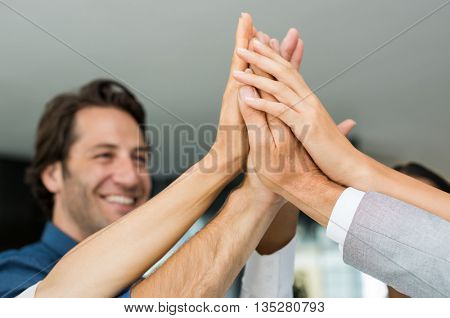 Group of multiethnic businesspeople giving high five. Close up of business hands giving high five in office. Happy business team high fiving in a modern office.