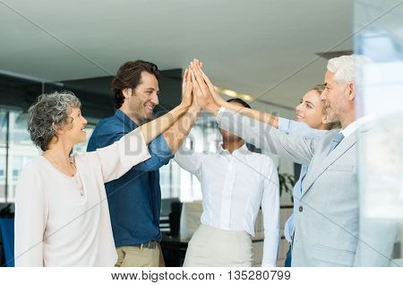 Businessmen and businesswomen celebration for good teamwork with high five. Business people group joining hands and representing concept of teamwork. Business team high fiving in the office.
