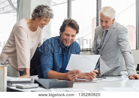 Business people working as a team at office. Business partners discussing documents and ideas during meeting. Team of businesmen and senior businesswoman feeling happy after seeing final contract.