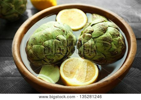 Artichokes in bowl on wooden table