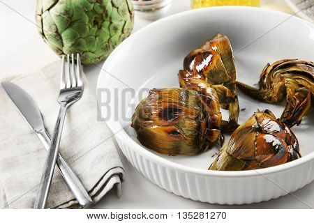Cooked artichokes with spices on pan