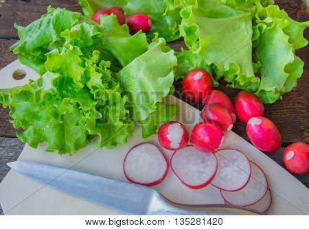 Radishes and fresh organic lettuce on a dark wooden background.