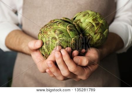 Man holding few artichokes