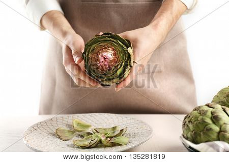 Man cooking artichokes on light background