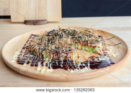 Concept of Japanese pizza on plate - Okonomiyaki.