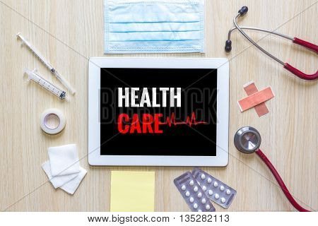 Top view of Health care word on tablet with stethoscope hypodermic syringe medicine mask and note.