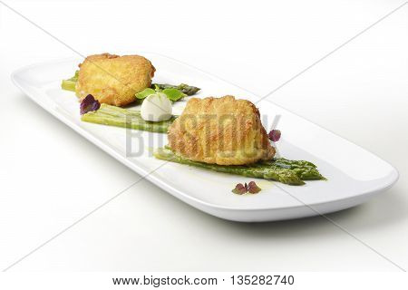 Fish dish fried Salt cod breaded Milanese style with asparagus