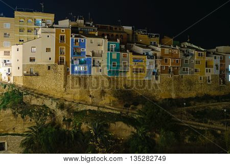 The skyline of Villajoyosa with the multicolored houses at night. Villajoyosa is a small village at the Costa Blanca at the Mediterranean Sea in Spain.