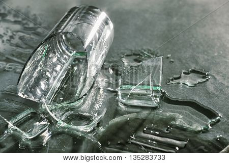 Broken overturned glass on gray background
