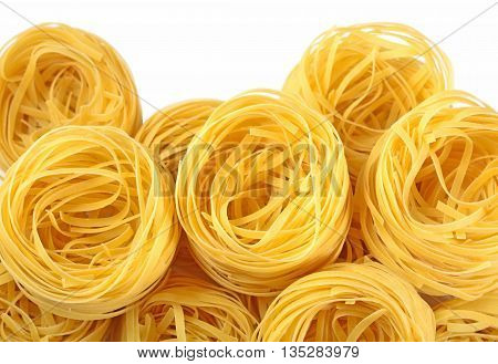 Uncooked Italian Pasta Tagliatelle Nests On A White