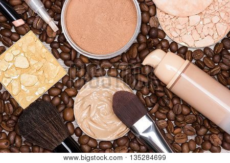 Basic makeup products to create beautiful skin tone and complexion. Concealers, liquid foundation, compact, loose and shimmer golden powder with brushes on coffee beans