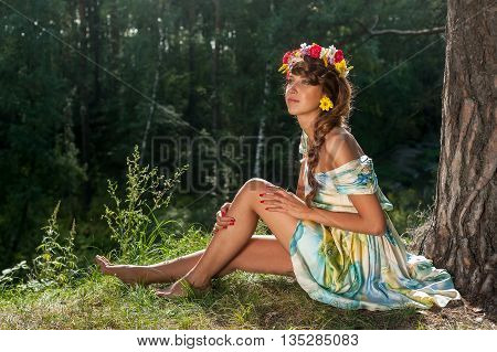 Attractive Woman Portrait with Wreath of Flowerssits near pine. Natural Beauty