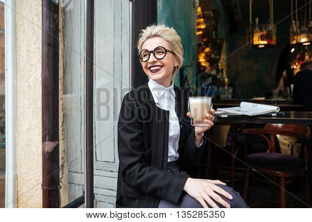 Close-up portrait with smiling stylish girl holding cup of coffee in cafe outdoors