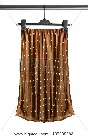Brown silk pleated skirt on clothes rack isolated over white