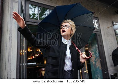 Close-up portrait of young beautiful woman with umbrella and coffee cup waving