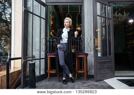 Stylish young fashion blogger posing at cafe