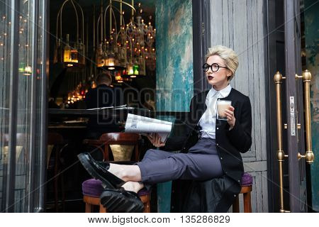 Beautiful stylish girl sitting in cafe with cup of coffee and magazine outdoors