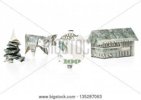 Concept of money in the form of a carved from dollars dollar sign origami tree piggy banks and houses built of hundred dollar bills isolated on white background