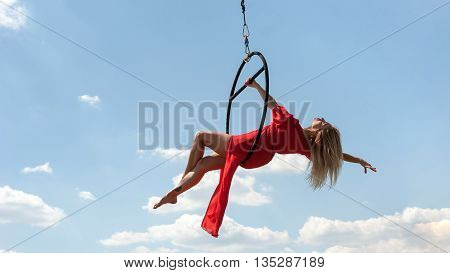 Elegant girl in a red acrobat beautiful dress performing gymnastic stunts on hoop outdoors against the blue sky with clouds