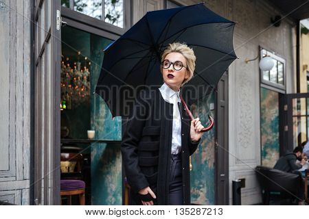 Young beautiful woman with umbrella outdoors at cafe