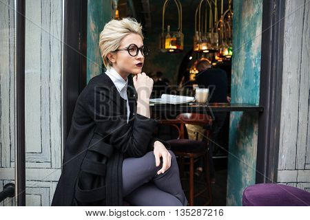 Portrait of stylish beautiful blonde woman thinking and sitting in cafe alone