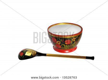 Wooden painted spoon and saltcellar with salt isolated on white background