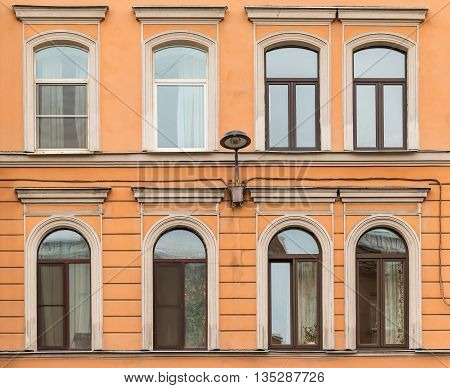 Several windows in a row and streetlight on facade of urban apartment building front view St. Petersburg Russia