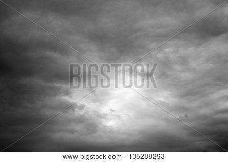 Sunshine through storm sky clouds. Thunderclouds over horizon dark gray.