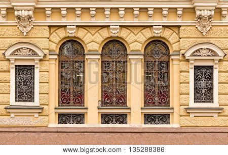 St. Petersburg Russia - May 16 2016: Several windows in a row with wrought grate on facade of urban office building front view