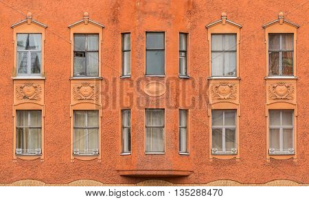 Several windows in a row and bay window on facade of urban apartment building front view St. Petersburg Russia