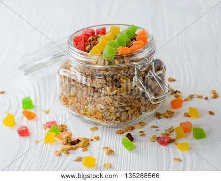 Muesli with dried fruit and candied fruit on a white wood background selective focus.
