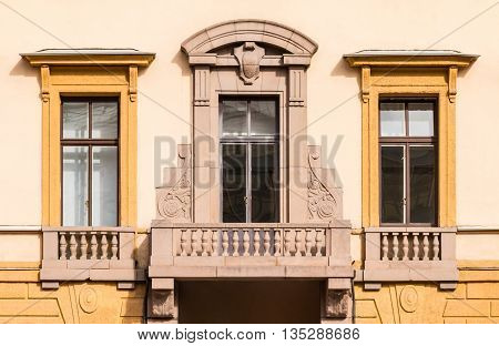 Three windows in a row and balcony on facade of urban office building front view St. Petersburg Russia