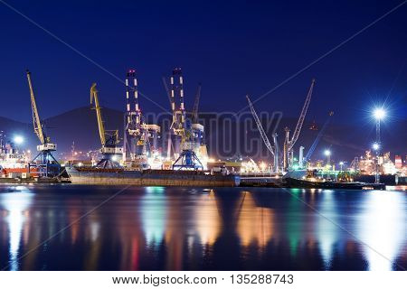 Cargo ships in the container terminal. Illuminated cargo port in Novorossiysk at night with container terminals cargo ships and cranes.