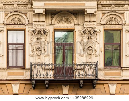 Three windows in a row balcony and sculptures on facade of urban office building front view St. Petersburg Russia