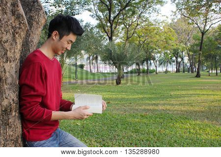 Young man reading in the park, spring time