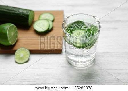 Infused cucumber water on wooden background